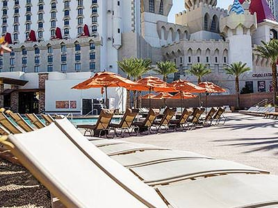 Sun loungers, and outdoor pool and the exterior of the Excalibur Hotel