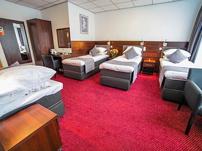 Four single beds in a hotel room, featuring a wardrobe right at the back of the room