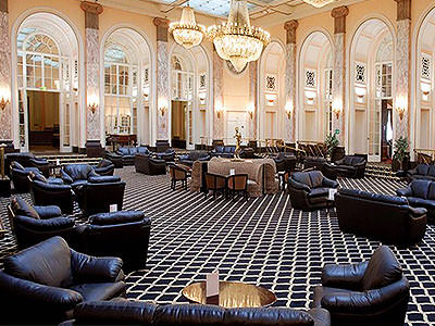 Black sofas and tables in a huge lobby with chandeliers