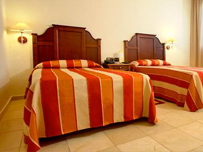 Two single beds with red striped bedding, in a hotel room