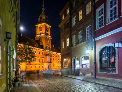 A street-lit Warsaw street at night