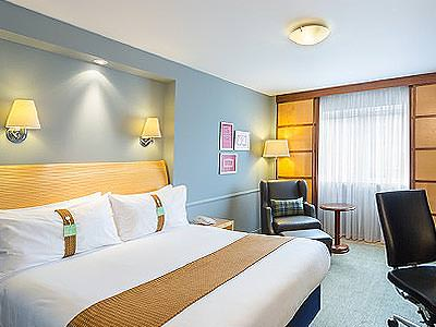 A double bed with a throw on top in a blue hotel room, facing a desk chair, with a chair in the corner