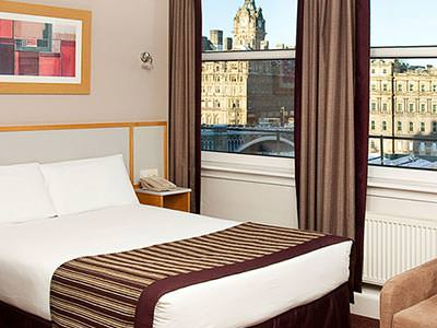 A double bed with a picturesque view of Edinburgh out of the window