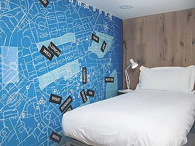 A single bed in a small room with a quirky map design on the wall