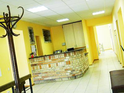 A lobby and reception area with a brick desk and yellow walls