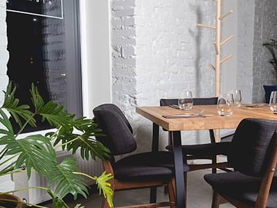 A small dining table surrounded by chairs and a plant