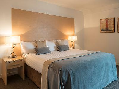 A double bed with white bedding and a blue throw on the bottom