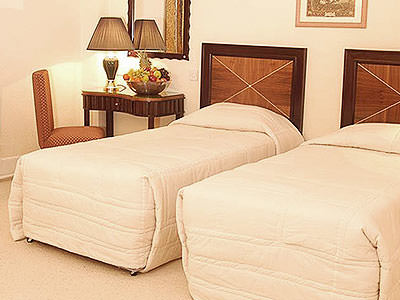 Two single beds in a hotel room, with a bedside table and chair next to one