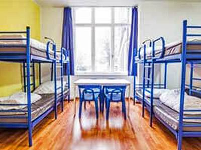 Blue bunkbeds along the sides of a room with a table and chairs in the middle