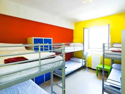 Three bunk beds in a yellow and red room