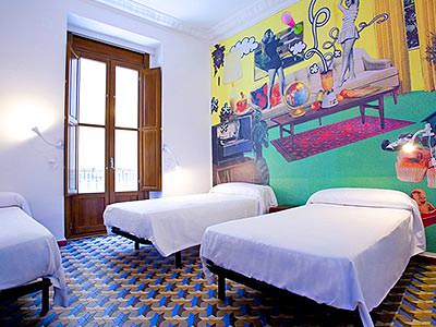 Three single beds within a bedroom with a quirky mural on the wall