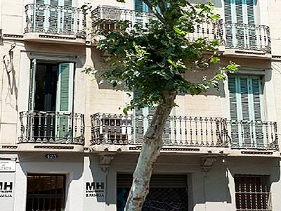 The exterior of Sagrada Familia Apartments, with a tree outside