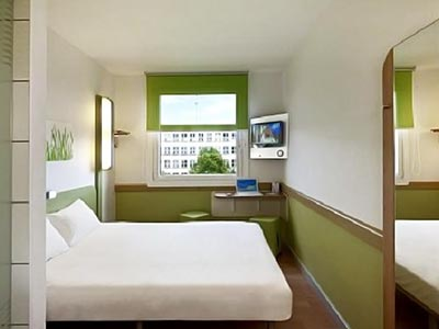 A double bed, with a pastel green and white colour scheme
