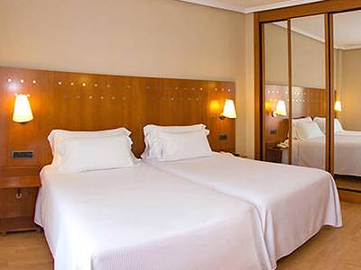 A twin room with wood paneling behind the beds, with lights on