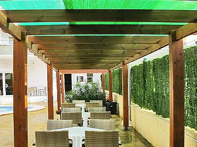 An outdoor seating area with wooden beams above and a swimming pool in the background