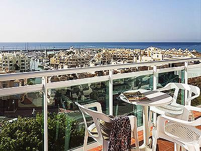 A view over Benalmadena from a balcony seating area, with the sea in the background