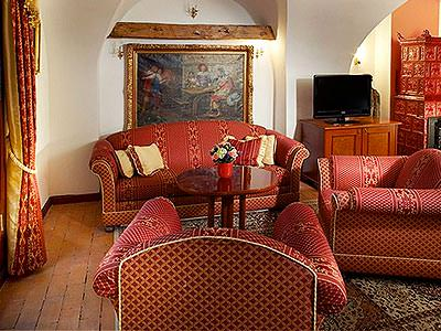 A sitting room with three comfortable sofas and an oil painting on the back wall