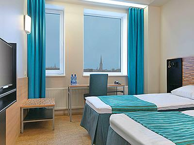 A guest room with two twin beds and blue highlights