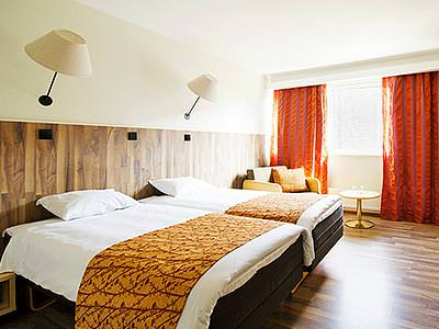 A spacious twin guest room with wall lamps and red curtains