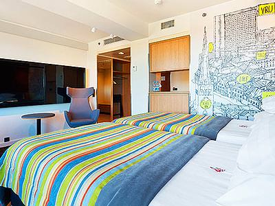 A guest room with striped bed covers and a map mural on the wall