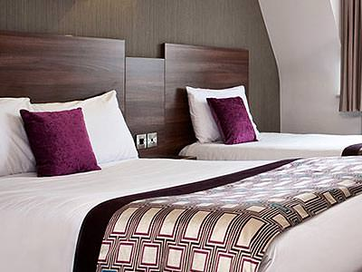 Two beds in a room with white, brown and purple colour scheme