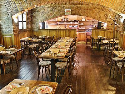 A restaurant, with tables set up for dinner, in a cellar of a building, with exposed brick
