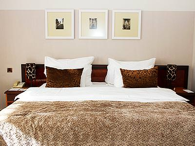 A white double bed with a brown throw and two brown cushions, with three pictures above the bed