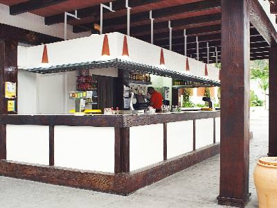 A white bar with dark wood beams, outdoors with plat pots in front