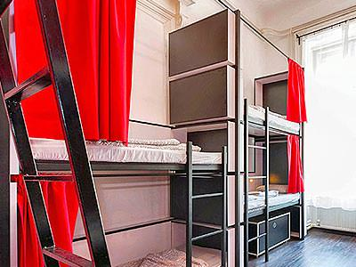 Bunk beds in a large room, with red curtains and storage space