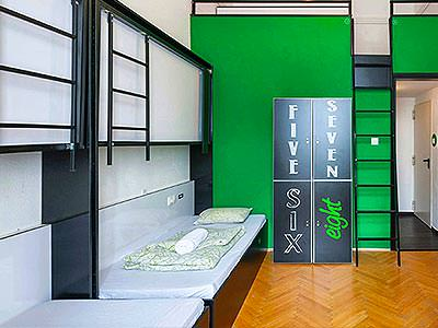 A room with dark green walls, beds and lockers with numbers written on