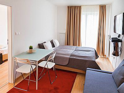 A double room with red rugs and a table with two chairs surrounding it