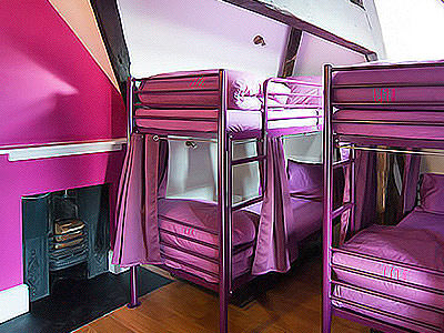 Two bunk beds in a purple room with exposed beams