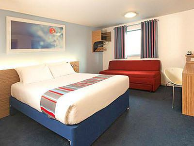 Hotel Bedroom with red sofa bed at Travelodge Clapham Junction