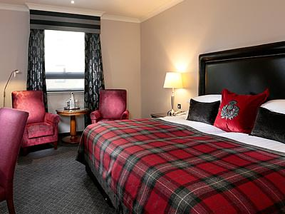 A bedroom with a huge double bed, and tartan bedding with matching cushions