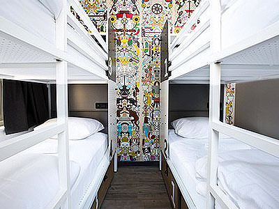White bunk beds in a room, with a colourful mural on the back wall