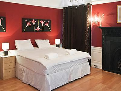 A bedroom with wooden flooring and black and red decor