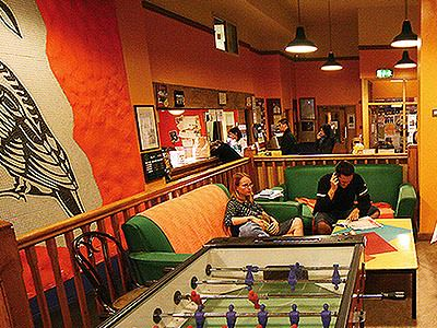 A bar and lounge area with foosball table at Avalon House Hostel