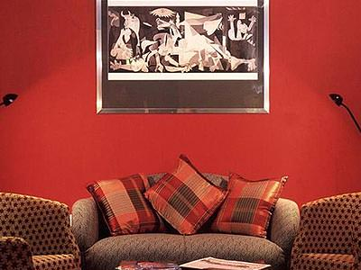 A red room with three sofas and a wall hanging above