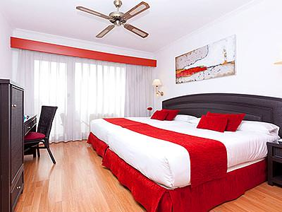 A double room with white bedding and a red runner along the bottom of the bed, with a large ceiling fan