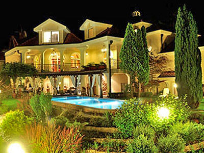 A night shot of a luxury villa, with trees and a pool outside