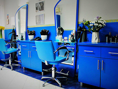 Blue retro modern hairdressers, with a blue seat in front of a mirror