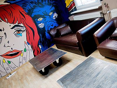 A seating area and wall mural at Corner Hostel