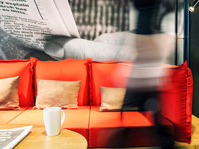 A red sofa, with a mug placed on top of a coffee table in the foreground