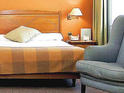 A bed with a comfortable chair at the foot of it