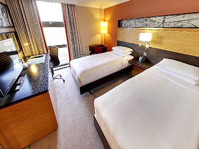 The interiors of a bedroom in Kensingtons Hilton hotel, with a flat-screen TV and two large beds