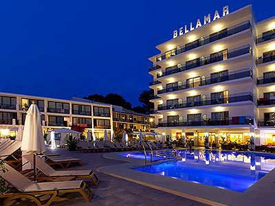 Sun loungers around an outdoor pool, outside the Bellamar Hotel at night