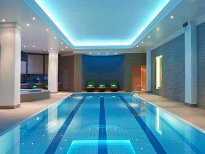 An indoor swimming pool in a blue-lit room