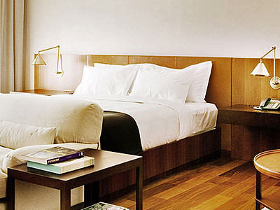 A double bed with a cream sofa at the foot of the bed, next to a wooden table with books on top