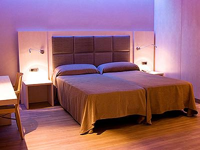 Two single beds in a hotel room, against a headboard lit-up with white lights
