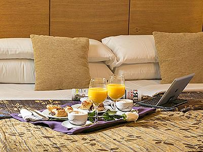 A breakfast tray with pastries and juice, next to a laptop, placed on top of a double bed